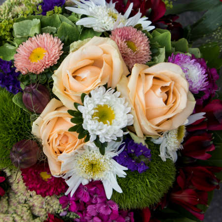 Bridal bouquet of, asters and orange roses, blue bells, green protea and carnations for sale Фото со стока