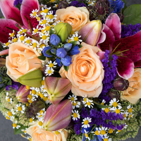 Bridal bouquet of, asters and orange roses, blue bells, green protea and carnations for sale