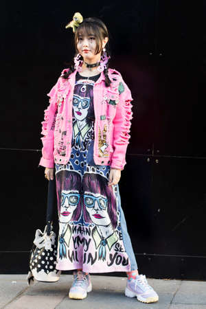LONDON, ENGLAND - September 15, 2019 Stylish attendees gathering outside 180 Strand for London Fashion Week. Chinese girl dressed in decora japanese street style in a pink denim jacket with toy dinosaur instead of a hairpin on her head