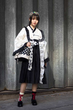 LONDON, ENGLAND - September 15, 2019 Stylish attendees gathering outside 180 Strand for London Fashion Week. Chinese girl dressed in traditional white and black kimono