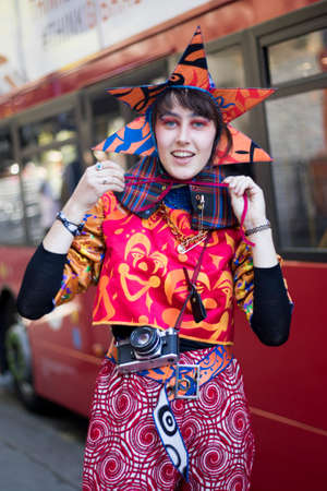 LONDON, ENGLAND - September 15, 2019 Stylish attendees gathering outside 180 Strand for London Fashion Week. A girl in a pointed wizard hat with star-shaped edges and a red-orange jumpsuit