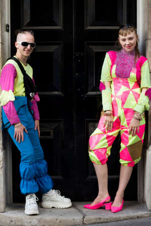 LONDON, ENGLAND - September 15, 2019 Stylish attendees gathering outside 180 Strand for London Fashion Week. Couple dressed in funny colorful party in neon colors. Редакционное