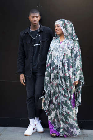 LONDON, ENGLAND - September 15, 2019 Stylish attendees gathering outside 180 Strand for London Fashion Week. Mom in a traditional African dress and son posing