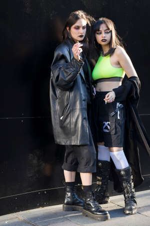 LONDON, ENGLAND - September 15, 2019 Stylish attendees gathering outside 180 Strand for London Fashion Week. Two girls dressed in black and green gothic costumes smoke by the wall