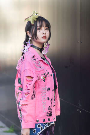 LONDON, ENGLAND - September 15, 2019 Stylish attendees gathering outside 180 Strand for London Fashion Week. Chinese girl dressed in decora japanese street style in pink denim jacket with toy dinosaur instead of hairpin on her head