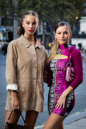 LONDON, ENGLAND - September 15, 2019 Stylish attendees gathering outside 180 Strand for London Fashion Week. Two girls in a beige and purple dress stand on the road