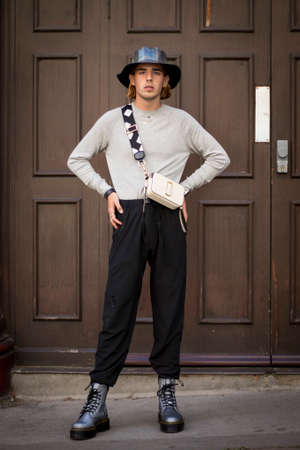 LONDON, ENGLAND - September 15, 2019 Stylish attendees gathering outside 180 Strand for London Fashion Week. Young man in a gray leather panama hat, sweater and hipster posing Редакционное
