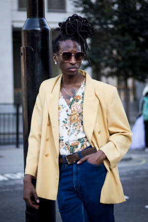 LONDON, ENGLAND - September 15, 2019 Stylish attendees gathering outside 180 Strand for London Fashion Week. Young man with dreadlocks in a yellow jacket