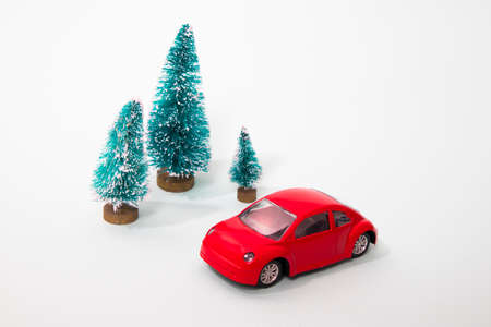 the Red toy car with a christmas tree on the roof, white background, shallow depth of field.