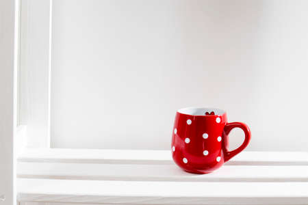 A red mug of polka dots stands on a white shelf on a sunny day. Stock fotó