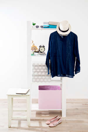 Storage system in the bedroom. Shelving with boxes, alarm clock, books, for small items and with a dress hanging on a hanger Stock Photo