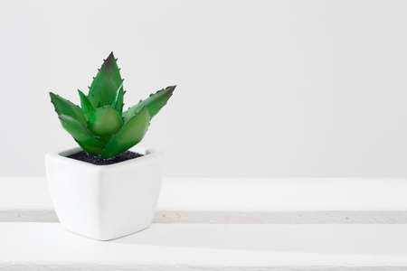 Artificial succulent in a white ceramic pot on a rack against the background of a notebook.