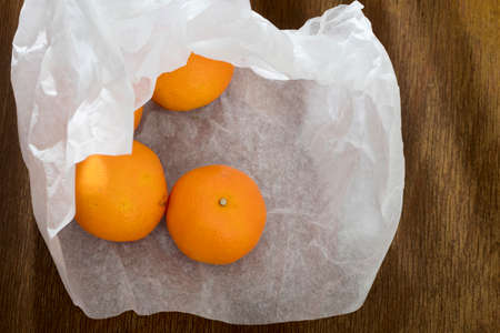 Tangerines in yellow crumpled craft paper on a dark wooden kitchen table