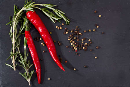 rosemary, pepper, chili on a black stone board as a decoration of the festive table