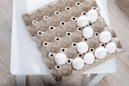 Chicken eggs in a white cardboard container lie on a beige wooden kitchen table.