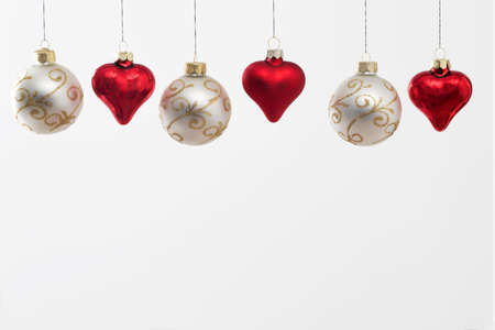 Gray Christmas balls with gold ornaments and red glass hearts hanging on the ropes. Greeting card. Copy space