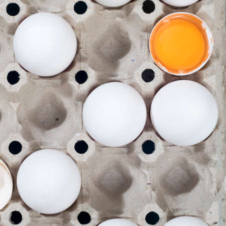 Chicken eggs in a white cardboard container lie on a beige wooden kitchen table. One egg is broken. A kitchen towel lies nearby