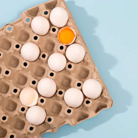 Chicken eggs in a white cardboard container lie on a blue wooden kitchen table. One egg is broken. A kitchen towel lies nearby
