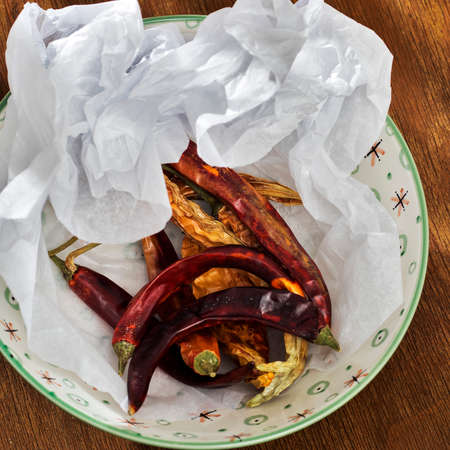 Dried hot peppers in crumpled craft paper in the kitchen as a decoration