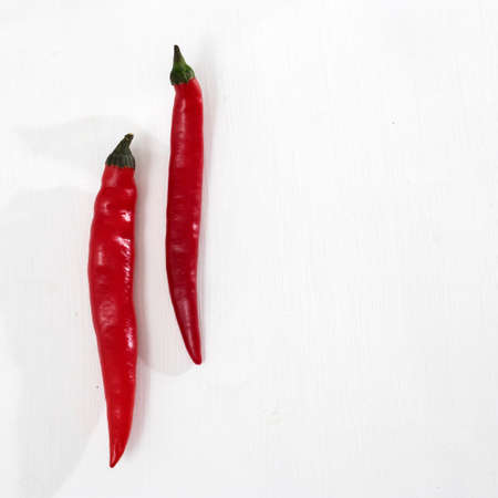 Two hot peppers on a white wooden table. Copy space