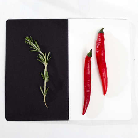 Rosemary branch on a black paper background. Card, Red pepper on the white