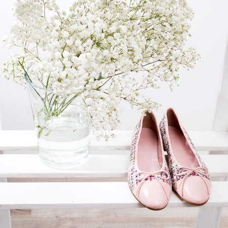 Bouquet of babys breath in a transparent glass vase and pink shoes of the bride on a shelf on a shelf
