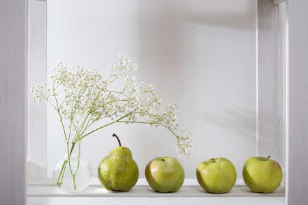 Wedding bouquet on a shelf with a pear