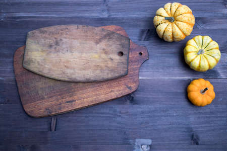 Orange pumpkins and leaves, top view on the brown wooden background , web banner with copy space in cutting board