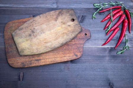 rosemary and chili pepper, top view on the brown wooden background , web banner with copy space. Set of chopping wooden boards with blank space