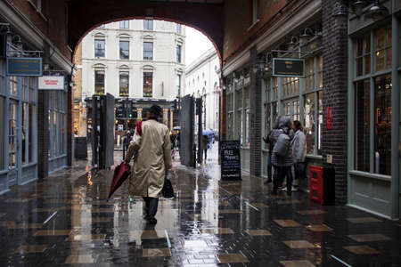 LONDON, UK - March 20, 2020: A classically dressed man in a gray cloak with an umbrella retires along the street
