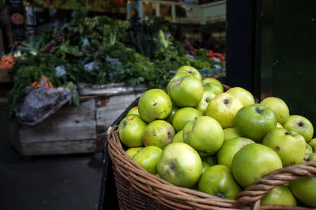 Green apples in a wicker basket at a market for sale. In the background are counters with seasonal vegetables.