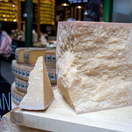 The rediscovery of Red Cow Parmigiano Reggiano. Pieces of chopped parmesan at a farmers market with a price tag