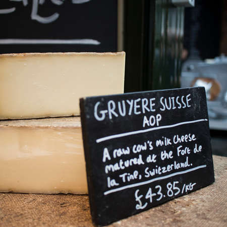 Gruyere cheese is generally known as one of the finest cheeses for baking, having a distinctive but not overpowering taste. For sale at farmer market Reklamní fotografie
