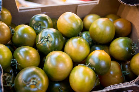 Quapaw Green tomatoes for sale on a farmers market stall