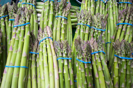 Bundled bundles of fresh asparagus on a counter for sale at a farmers market