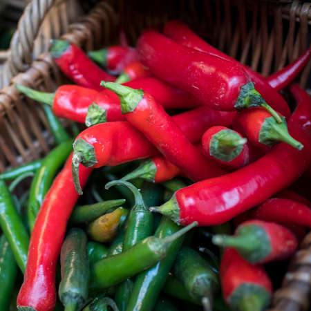 Green and red chilli hot peppers in a wicker basket at a farmers market Reklamní fotografie