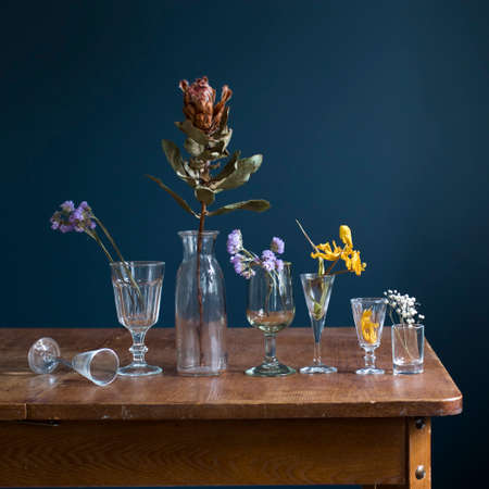 Dried flowers in glass glasses on a wooden table opposite a dark blue wall. Art card. Design. Copy space.