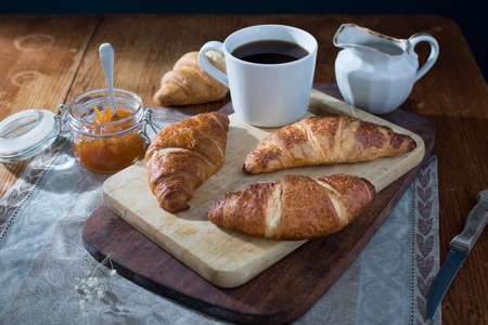A large cup of coffee, milk jug, a can of apricot jam and four croissants is on a wooden board for cutting on a table in dark colors. Morning. Breakfast. Copy space.