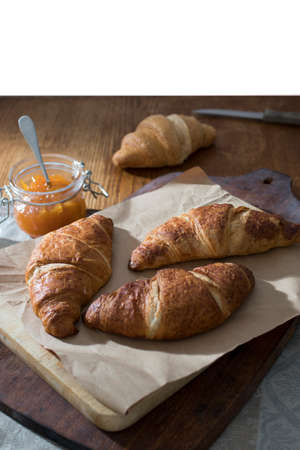 A four croissants, a can of apricot jam is on a wooden board for cutting on a table in dark colors. Morning. Breakfast. Copy space.