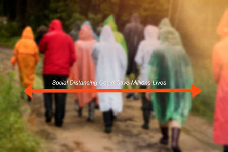 White text is on a blurred photo with unrecognizable people in color raincoats go to the forest. Social distancing could save millions of lives. Covid-19 virus outbreak. protection and safety concepts Standard-Bild