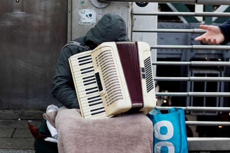 London, UK - 23 February 2020 Unrecognizable Romanian street musician bowed his head on an accordion while resting