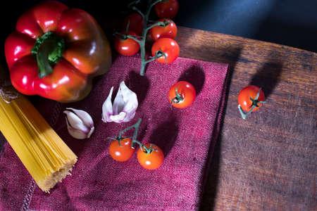 Italian food background with cherry vine tomatoes, pepper, spaghetti, garlic, peppercorns and garlic on the dark background