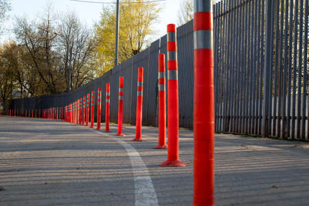 Red bounding posts along the road against a gray trellised fence. Spring time