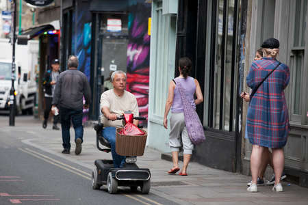 LONDON, UK - September 17, 2019: A man rides on a scooter for the elderly in Bricklane shopping Éditoriale