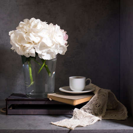 White hydrangea in a glass vase with a small cup of coffee on a book with a notebook on a gray craft background. . Copy space