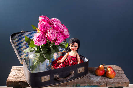 A bouquet of red roses in a glass vase and an old doll in a vintage suitcase on a blue background, two pears on a wooden ruined surface of the bench. Copy space