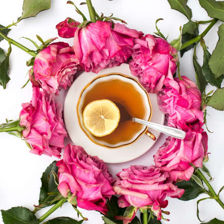 a bouquet of red roses surrounds a cup of tea with lemon and saucer. Circle, Copy space