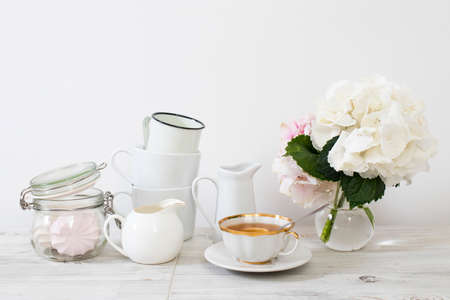 Ball-shaped white hydrangea in a round glass vase, a set of light dishes, milk jug, porcelain and enameled cups, a jug for a greeting card on a white background. Imagens