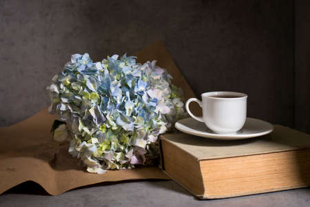 A branch of green pastel hydrangeain with white cup of coffee and vintage book on a on a gray craft vintage background. Copy space
