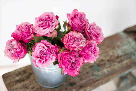 Bouquet of red roses in a tin bucket on a white wall background on a wooden wrecked surface of the bench. Copy space